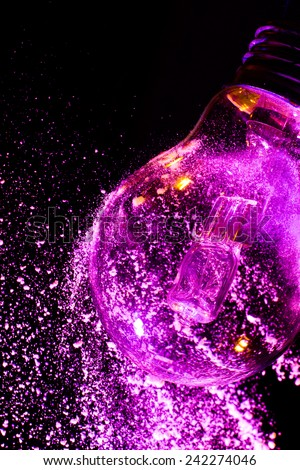 Abstract Purple colorful light bulb with powder on black background close up