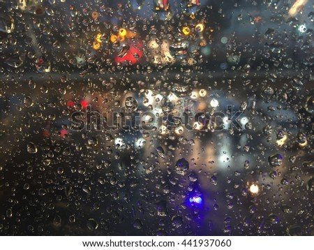 Abstract Raindrops on the mirror with street bokeh lights background #441937060