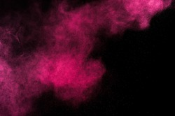 Abstract red and pink powder explosion on black background.