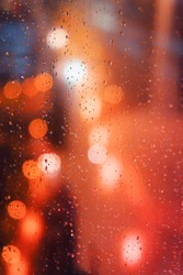 Abstract red bokeh image from vehicle through rainy window