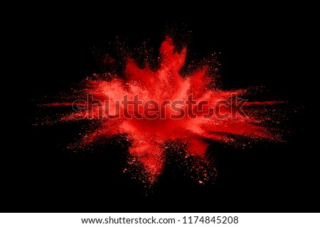 Abstract red powder explosion. Closeup of red dust particle splash on white background.