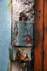 Abstract rusty door hinge with peeled paint