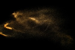 Abstract sand cloud. Golden colored sand splash agianst dark background. Yellow sand fly wave in the air. Sand explode on black background ,throwing freeze stop motion.