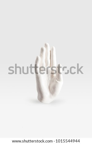 abstract sculpture in shape of human arm in white paint on white surface