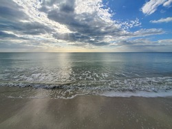 Abstract seascape panoramic background - late afternoon. Calm seas/ocean in the bottom of the frame. Minimalistic simple background image, blue and yellow colors, clouds and sky