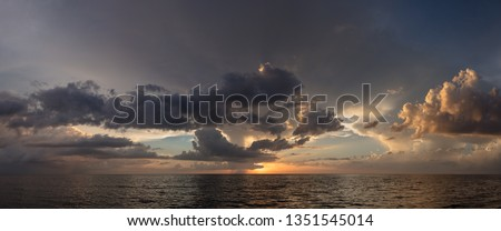 Abstract seascape panoramic background - Orange color in the sky, sunset late afternoon. Calm seas/ocean in the bottom of the frame. Minimalistic simple background image, blue and yellow colors. #1351545014