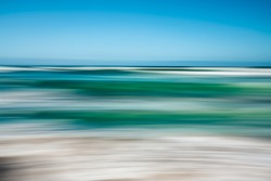Abstract seascape with blurred panning motion. Image displays blue and light turquoise split-toned color scheme.