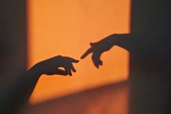 Abstract shadow silhouette of gesture touch by humans palms from sunbeam on wall during posing wrist and fingers. Creation of Adam metaphor by Michelangelo