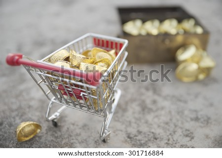 Abstract shallow DOF of gold treasuring into treasure chest by pushcart with a gold drop behind. The chinese words are crafted into gold with meaning of good fortune, best of luck, and good health.