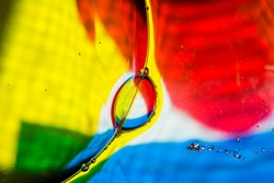 Abstract shapes created by several soap bubbles attached on a colorful background.