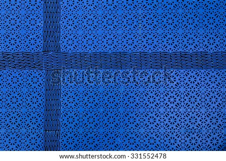Abstract shot of a floor mat pattern with cross shaped part, resembling a Nordic Cross.