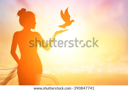 Abstract silhouette of bird flying out of lady hand on beautiful background.freedom concept