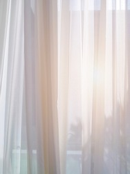 Abstract silhouette scene with white sheer curtain inside window in living room, white sheer curtain bright up with sun flare outside to inside, soft and light pleats fabric pattern.