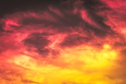 abstract sky, red pink and orange yellow color in blurry soft clouds in overcast sky, burn sky