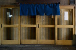 Abstract soft focus of traditional Japanese restaurants and shops style front view, curtain vivid blue fabric hangs in  front and on top of Japanese wooden slide door.