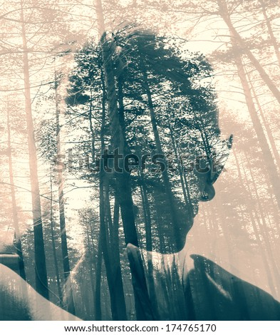 Abstract soft focused duotoned double exposure portrait of woman and black forest