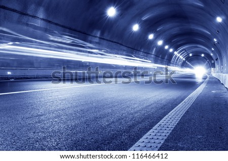 Abstract speed motion in urban highway road tunnel, blurred motion toward the central. Shot from a slow moving car