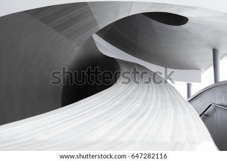 abstract spiraling handrail of a wooden staircase in a modern design building