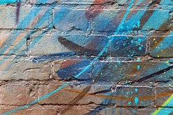 Abstract splashes, drops of paint on a brick wall. Street modern style. Street art. Graffiti. Painted walls. Vandalism. Randomness