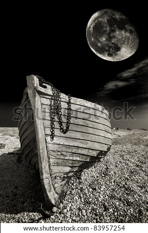 abstract, spooky, warm toned black and white image of an abandoned wooden fishing boat on the beach at Dungeness, UK, with a harvest moon in the background