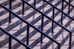 Abstract stairs and shadows.  Concrete staircase with steel railings throwing hard shadows. Patterns from shadows and railings on the steps. Urban geometry. Confusing mix of shadows with real objects