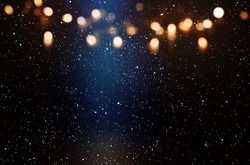 Abstract starry sky background with blue light beam and golden bokeh for a new year concept