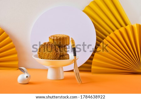 Abstract still life Mid autumn festival snack and drink moon cake on yellow  and orange background.