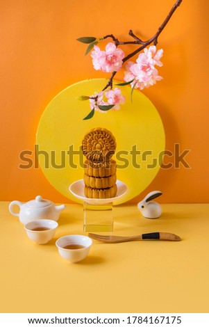 Abstract still life Mid autumn festival snack and drink moon cake on yellow background.