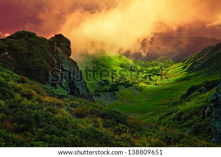 abstract stone giant and orange fog over the green Carpathian mountain valley