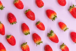 Abstract strawberry pattern. Ripe red strawberry fruits lies in diagonal lines on purple background. Top view. Summer food theme.