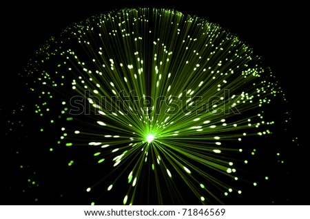 Abstract style overhead view of illuminated fiber optic strands against black.