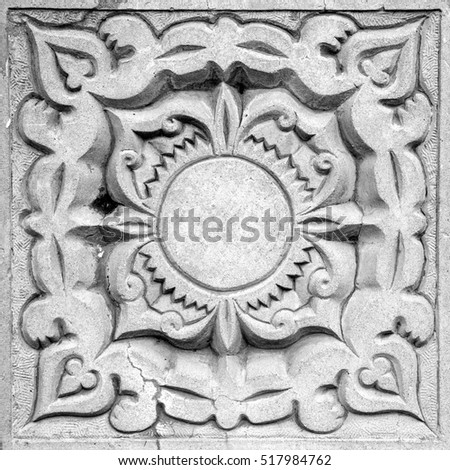 abstract sun ornament, a stone bas-relief on the wall