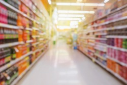 Abstract supermarket aisle with soft drink bottles product shelves blurred background