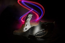 Abstract surreal concept. Giant animal bone in dark. Night with fog and light on background. Selective focus