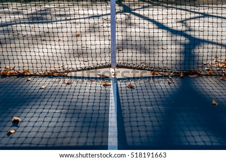 Abstract tennis court center with fallen leaves clay court. Isolated tennis court net. Light and shadow on center court. Minimal design and art. Abstract outdoor sports. Fall season on tennis court.