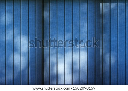 Abstract texture background of light filtering blue fabric vertical blinds showing silhouette shadows of outdoor trees with defocused bokeh