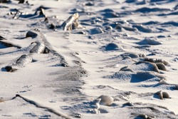 Abstract texture with frozen waves of lake water mixed with sand and covered with snow