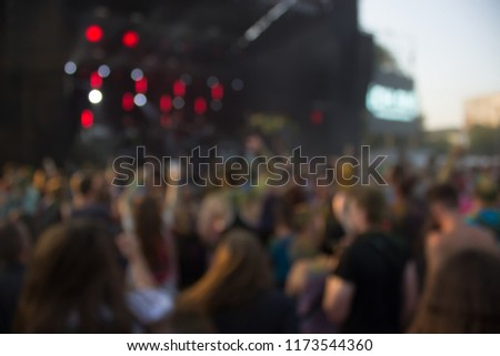 abstract unfocused blurred open air music festival and crowd of people near stage in evening bright sunset time with light glares