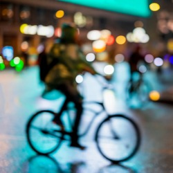 Abstract unrecognizable man silhouette, riding bikes, night city, illumination bokeh, motion blur. Healthy lifestyle, leisure activity concept.