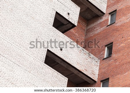 Abstract urban architecture fragment, gray and red brick walls with balcony and windows