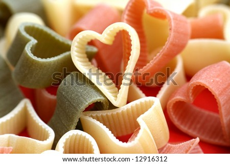 Abstract valentine or food background with uncooked noodles n diffrent colors looks like hearts