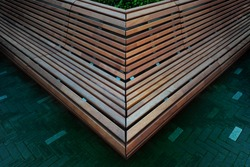 Abstract view of an urban wooden bench. Corner view of an outdoor bench at the city square. Outdoor furniture detail background image.
