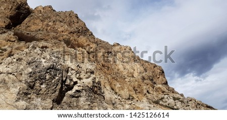 Abstract view of mountainside against cloudy sky #1425126614
