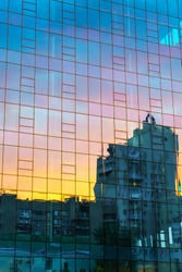 Abstract view of sunset sky reflection in modern business glass wall building.