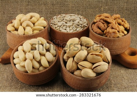 Abstract view of the mixture of nuts in a round wooden form on the background of natural fabrics