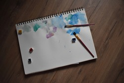 Abstract watercolor painting customizable with wooden background. Different colors plashing in the paper with two paintbrush