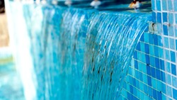 Abstract waterfall background, a swimmingpool with blue mosaic tiles