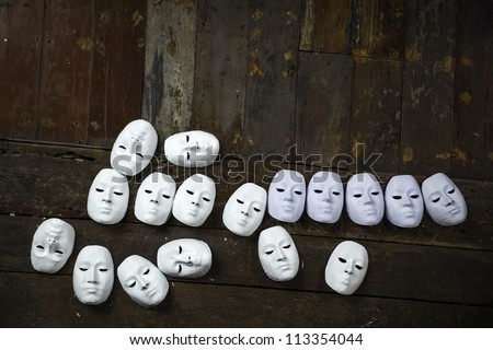 Abstract white masks on wooden background
