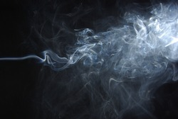 Abstract wisps of smoke on a black background.