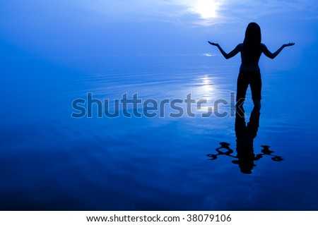 Abstract women silhouette in the sea looking at sun with arms open.